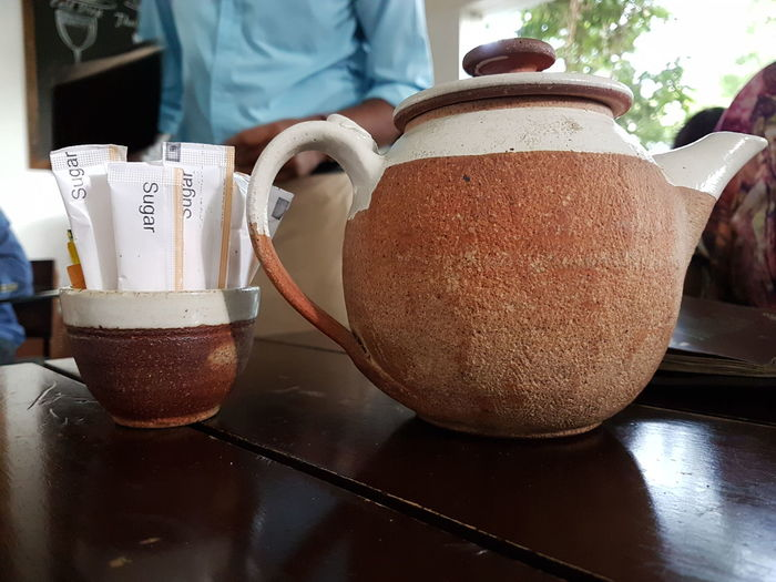Close-up of coffee pot by sugar packets in bowl on table