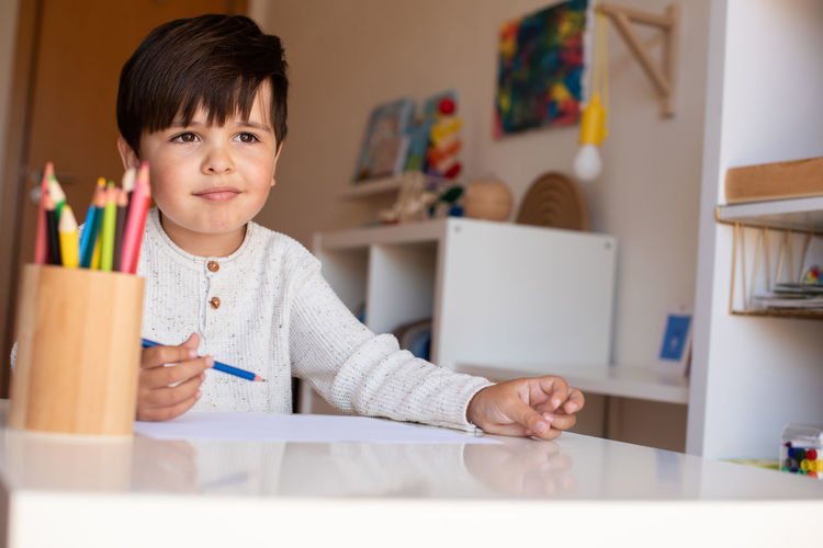 Portrait of boy on table at home