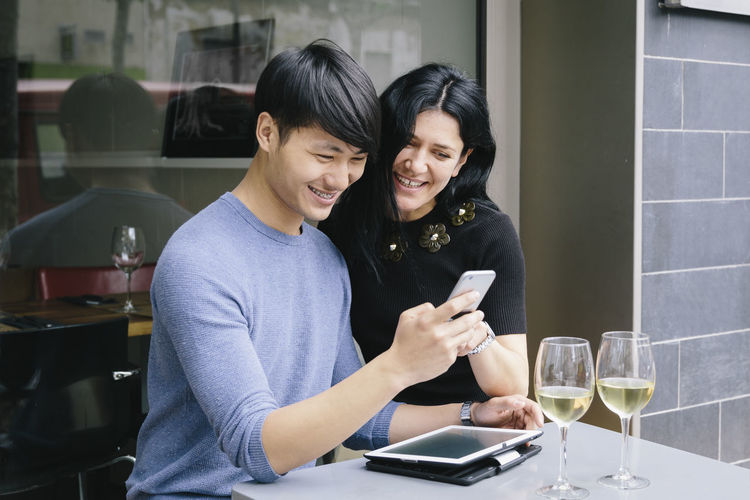 Smiling couple using mobile phone while sitting at sidewalk cafe