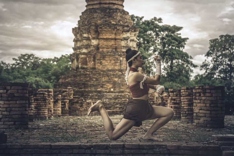 Woman in traditional clothing kickboxing against historic building