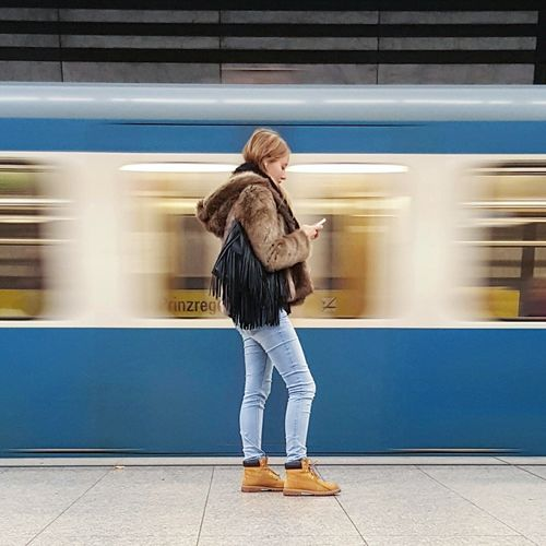 Side view of woman using smart phone while standing against train