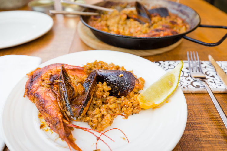 Seafood Paella in a traditional pan and served on white plate Food And Drink Ready-to-eat Table Plate Close-up Serving Size No People Meal Dinner Spanish Spanish Food Paella Paellas Paella De Marisco Marisco Barcelona Prawn