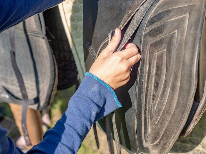 An unrecognizable girl setting horse saddle at horse stable. setting pad and strips of stirrups