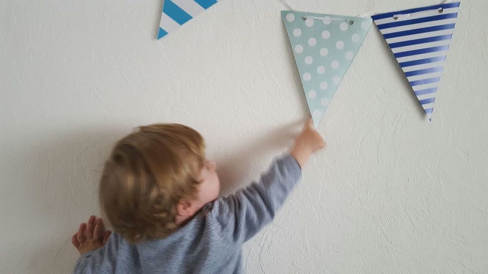 Fun Childhood Child Children Only Blond Hair Home Interior Human Body Part Indoors  Children's Clothing Playing Stripes Pattern Dots Flags Baby Shades Of Blue Celebration Birthday Party Interior Design Decoration Not Looking At The Camera Pointing Finger Showing Children Playing One Boy Only Garlands