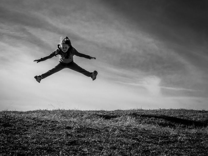 Girl jumping mid-air over grass against sky