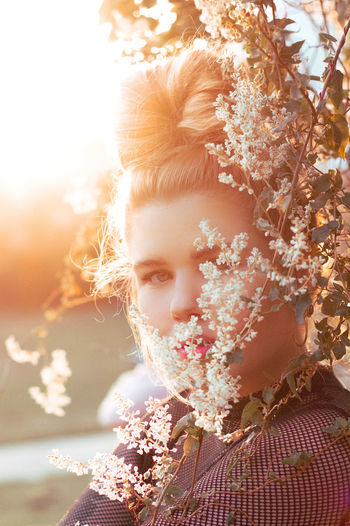 Close-up portrait of girl with flowers on plant