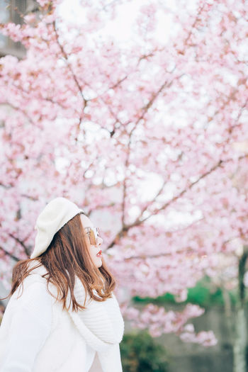Low angle view of woman standing by pink flowering tree