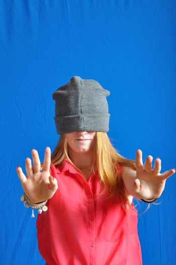 Woman gesturing while wearing knit hat against blue backdrop