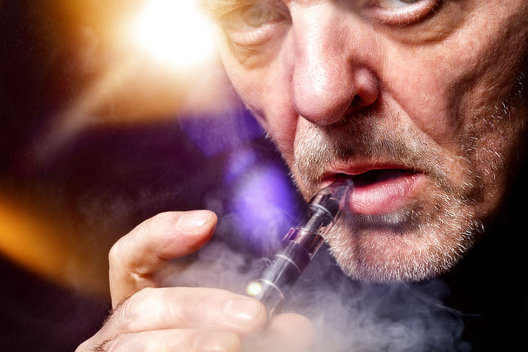 Portrait Of Mature Man Smoking Electronic Cigarette
