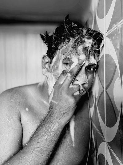 Portrait of shirtless young man with soap sud bathing in bathroom