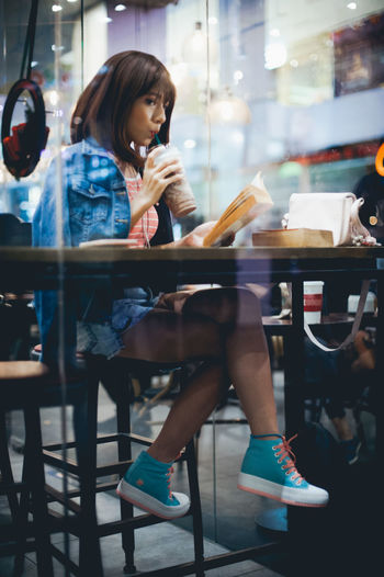 Cafe Coffee - Drink Communication Full Length Holding Illuminated Indoors  Mobile Phone Night One Person People Real People Sitting Technology Using Phone Wireless Technology Women Young Adult Young Women