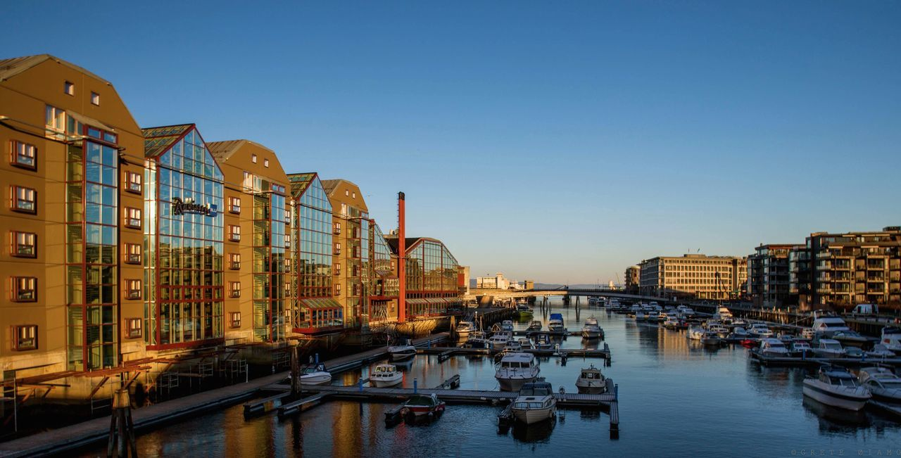 architecture, built structure, building exterior, clear sky, water, transportation, nautical vessel, mode of transport, waterfront, city, reflection, no people, outdoors, travel destinations, day, sky