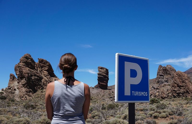 Rear View Of Woman Standing By Parking Sign At Desert Against Sky