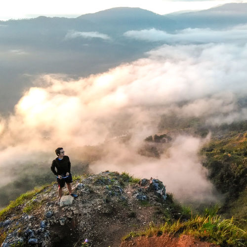 High angle view of young man standing on mountain during sunset