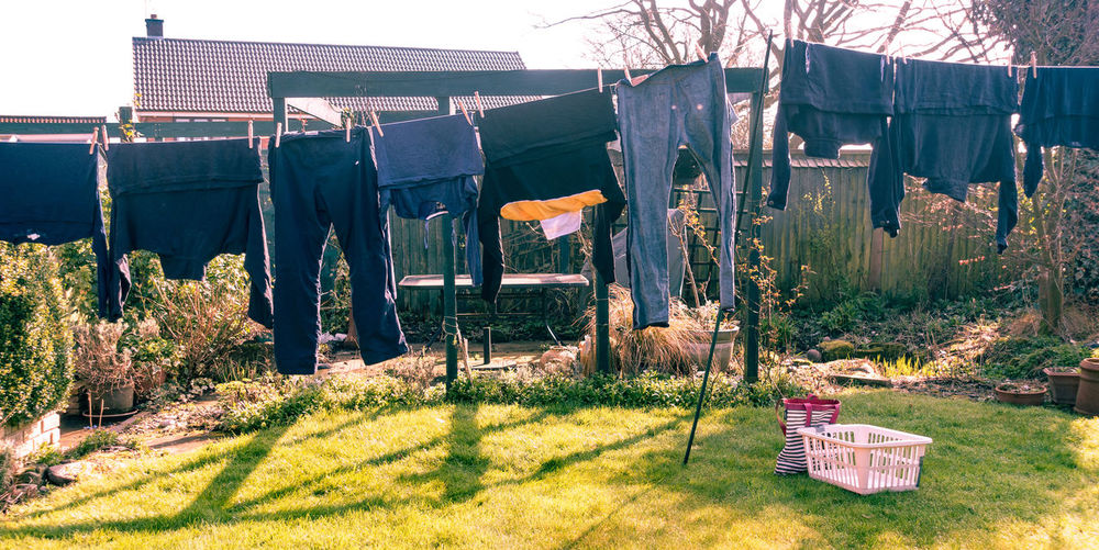 Clothes drying on a washing line in a residential back garden. Fresh Air Hanging Residential Garden Back Garden Clothes Clothesline Clothing Clothing Line Day Dry Drying Grass Hanging Laundry Laundry Basket Lawn Nature No People Outdoors Plant