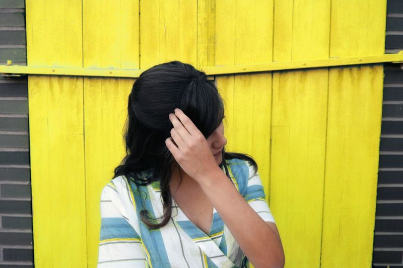 Close-up of woman against yellow wall