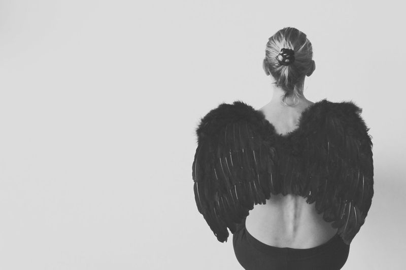Rear View Of Woman With Angel Wings Sitting Against White Background