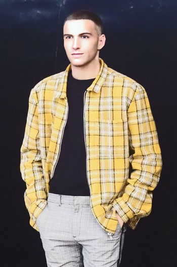 The Dancer Beautiful People Black Background Casual Clothing Checked Pattern Clothing Contemplation Fashion Front View Fully Unbuttoned Gray Handsome Indoors  Looking At Camera Menswear One Person Plaid Shirt  Portrait Real People Standing Studio Shot Three Quarter Length Young Adult Young Men