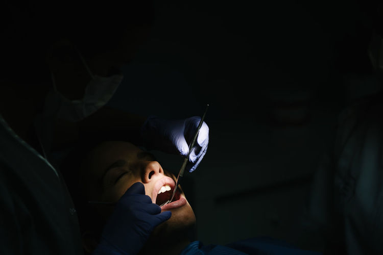 Close-up of dentist examining woman in clinic