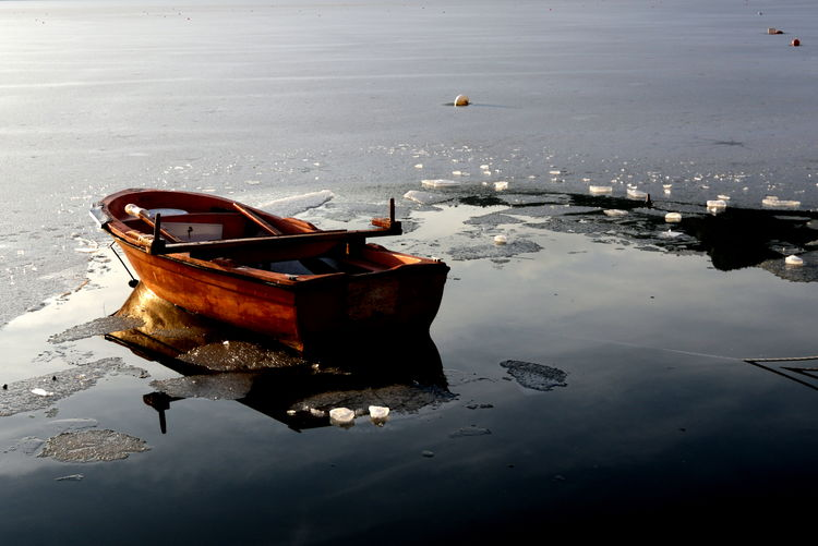 High angle view of frozen boat moored at lake during winter