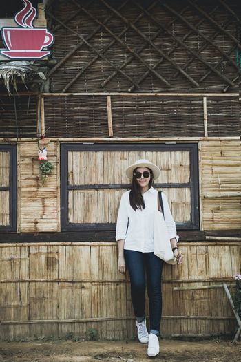 Portrait of woman in sunglasses standing against barn