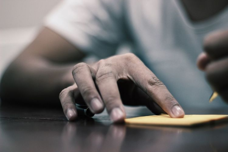 Midsection of man holding adhesive note on table