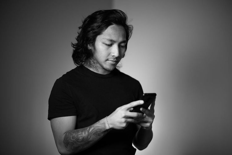 Mid adult man using smart phone against gray background