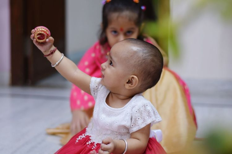 Close-Up Of Cute Baby Girl Holding Diya At Home