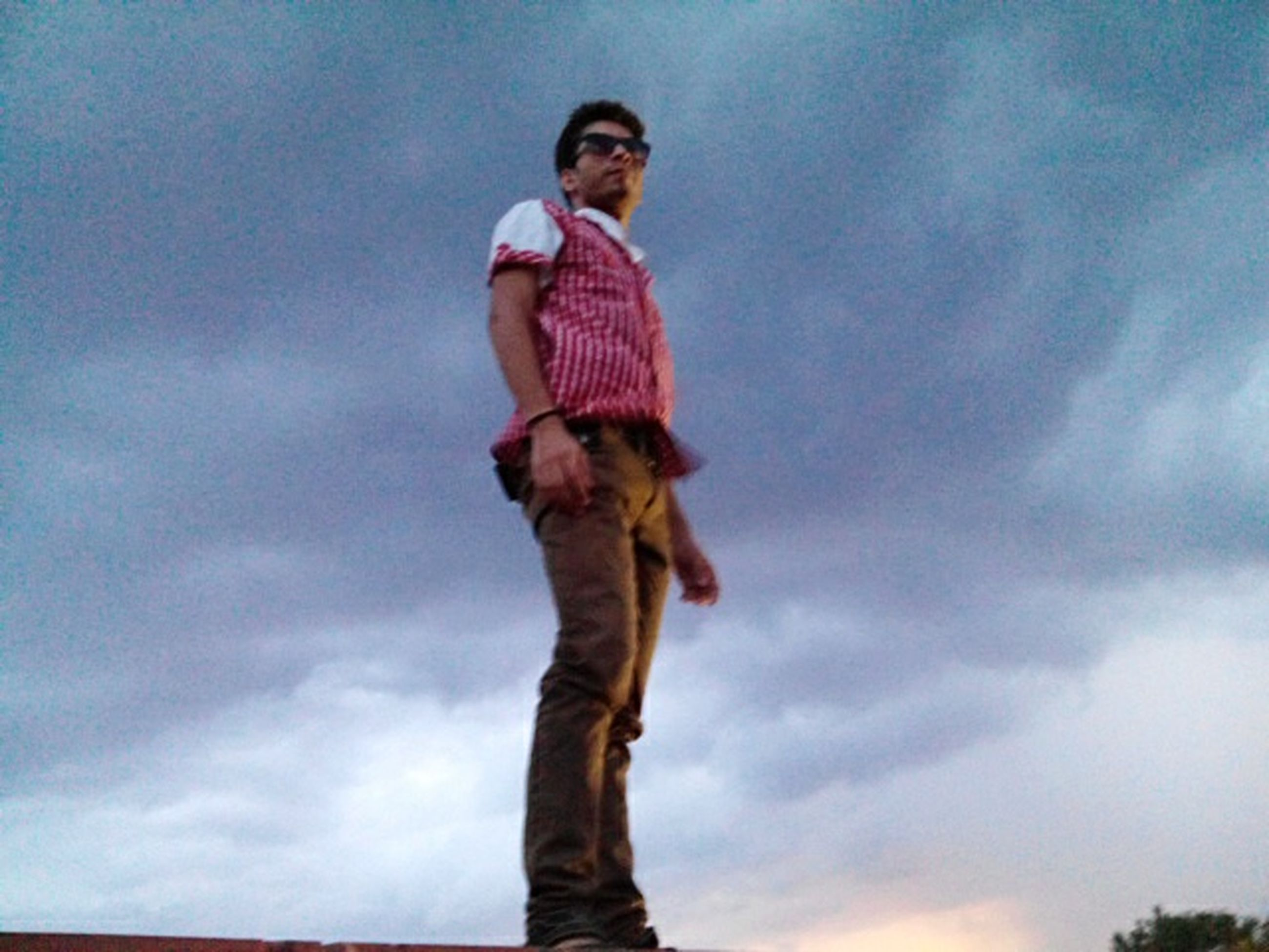 low angle view, sky, cloud - sky, full length, standing, looking at camera, portrait, front view, casual clothing, person, lifestyles, young adult, cloud, cloudy, young men, leisure activity, one animal, three quarter length