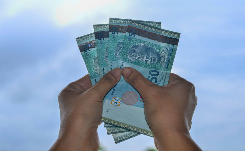 Cropped Hands Holding Paper Currency Against Sky