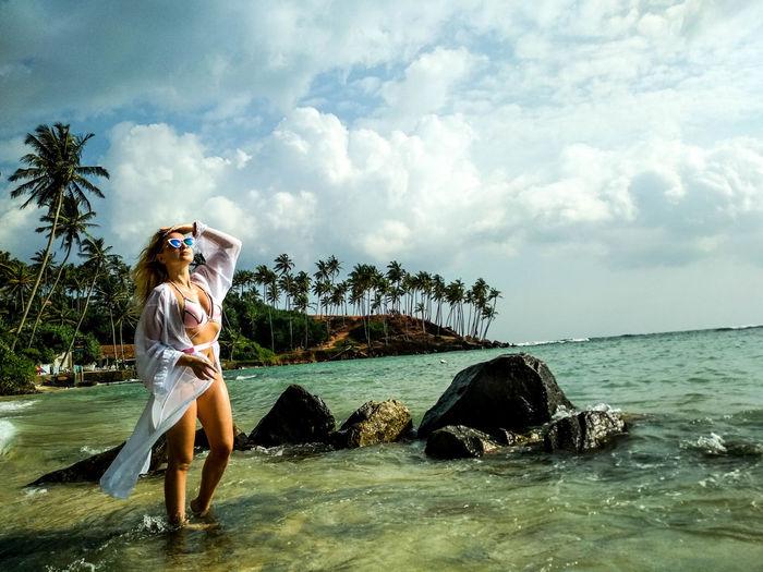 Woman on sea shore against sky