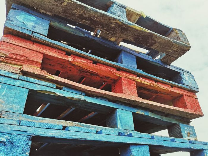 Tower of coloured pallets Wooden Pallet Pallets Blue, Red Wood High Looking Up Urban Urbanphotography Damaged Huawei P20 Pro Photography Huawei P20 Pro Architecture Sky Built Structure Construction Deterioration Abandoned Discarded Deserted