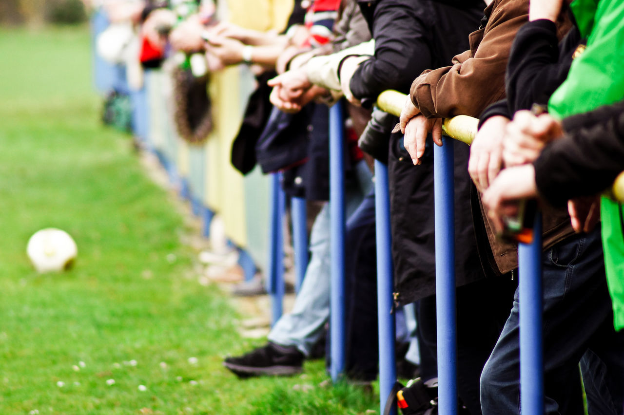 Spectators standing by railing on playing field