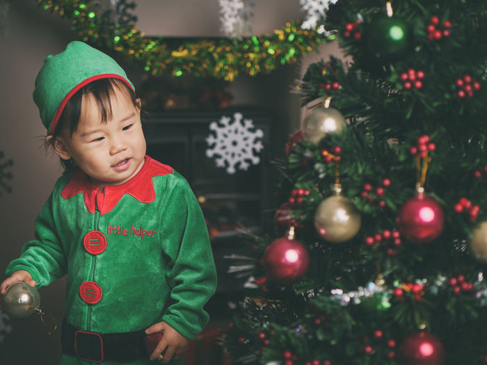 Cute baby girl by christmas tree at home
