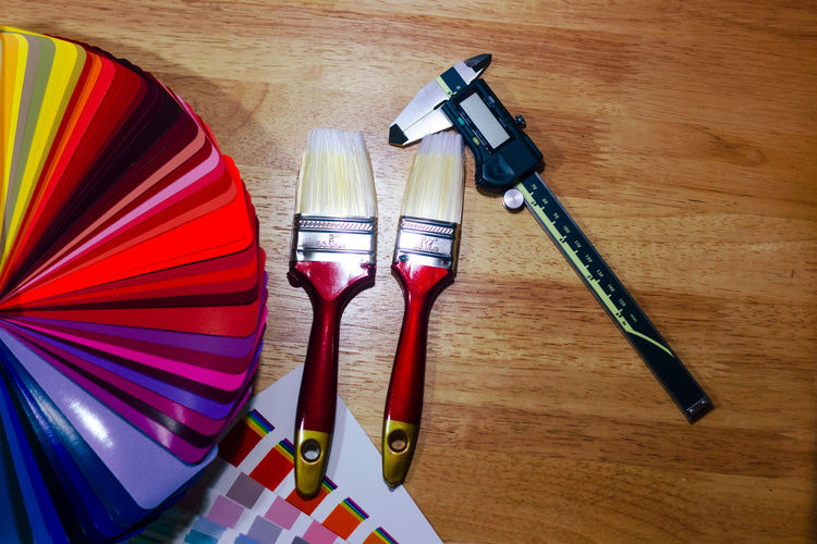High angle view of paintbrushes by color swatches on table