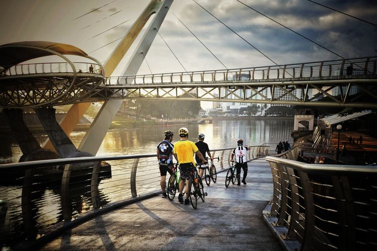 People riding bicycle on bridge in city