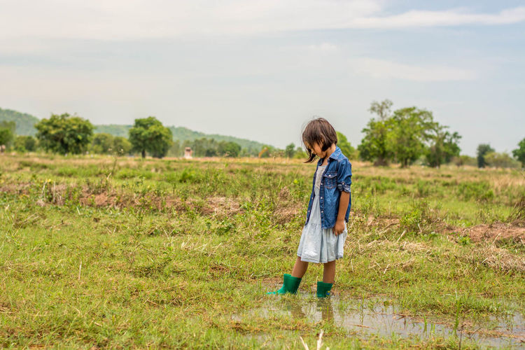 Beauty In Nature Casual Clothing Childhood Day Field Full Length Grass Nature One Person Puddle Real People Sky Standing Wellies