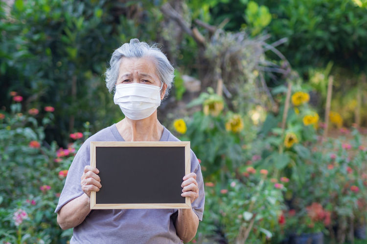 Elderly woman standing holding a black label and wearing face mask while standing in a garden