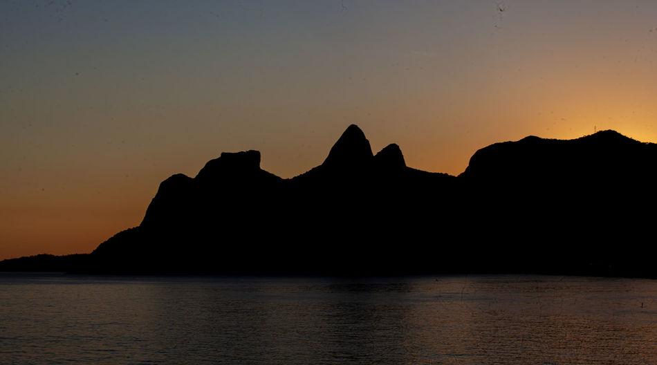 Silhouette mountain by sea against orange sky
