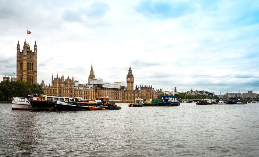 Boats on thames river against houses of parliament in city