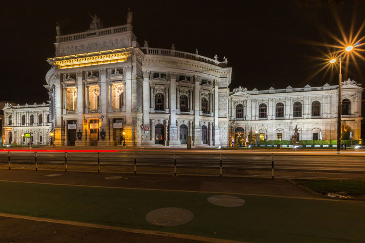 Light trails on road against historic building