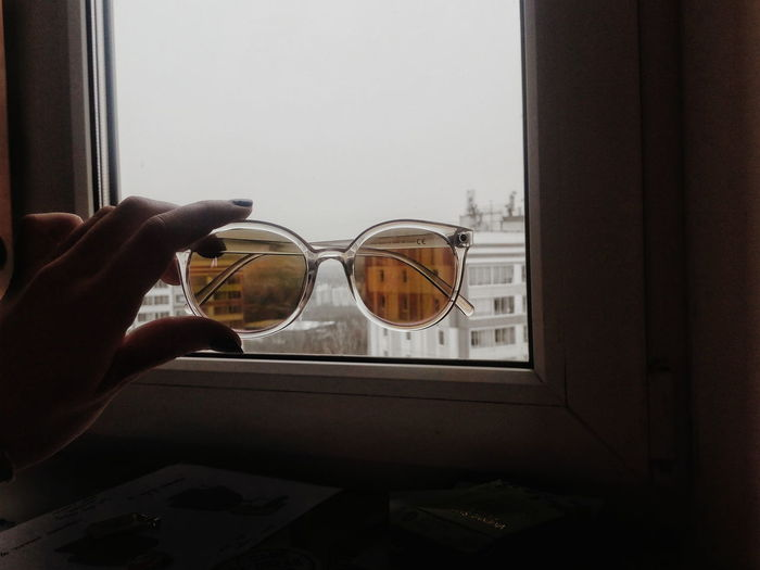 Close-up of hand holding sunglasses against window