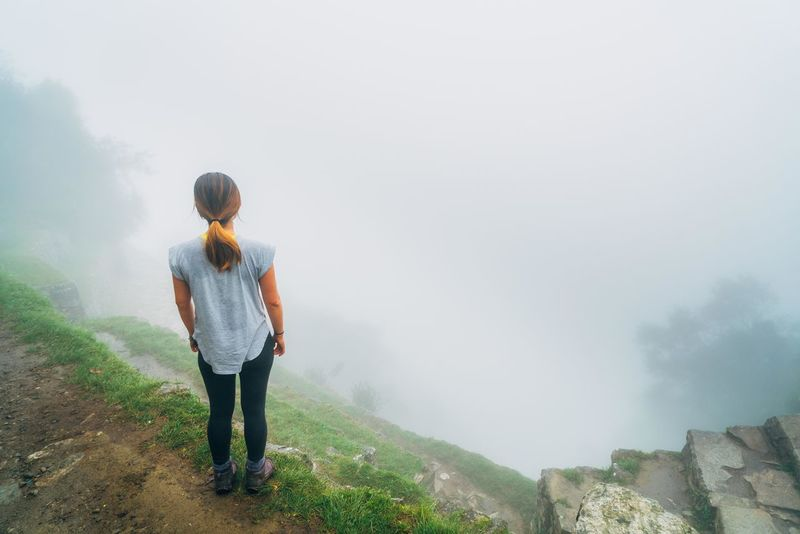 Lost In The Landscape Adult Adults Only Adventure Backpack Beauty In Nature Casual Clothing Day Fog Full Length Hiking Hooded Shirt Landscape Leisure Activity Lifestyles Mountain Nature One Person One Woman Only Outdoors Real People Rear View Scenics Standing Walking Women