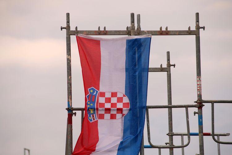 Croatian flag on pole against cloudy sky