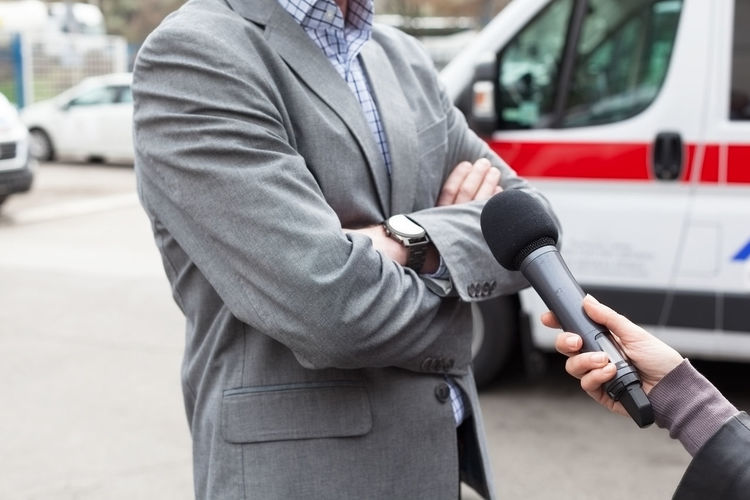 Cropped Hand Of Female Reporter Interviewing Man On Street