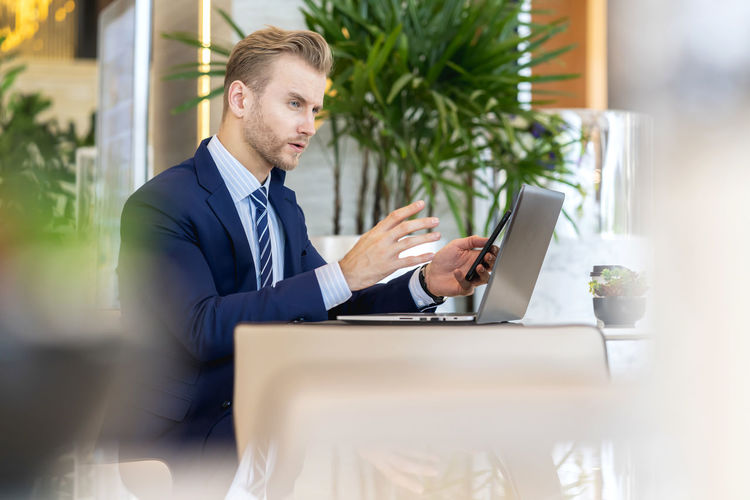 Side view of handsome businessman using phone and laptop on office desk