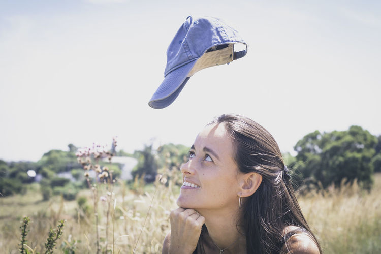 Portrait of young woman looking up towards levitating cap