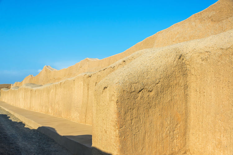 Adobe wall of old ruin during sunny day