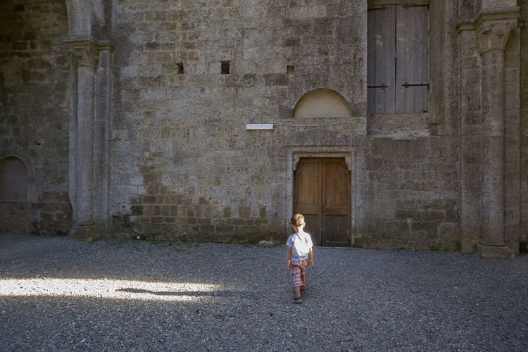 Rear View Of Boy Walking On Street By Old Building