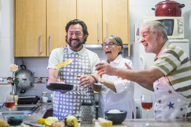 Happy Family Cooking Food In Kitchen